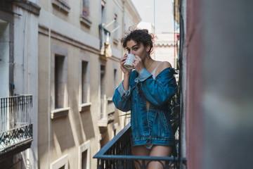 Laughing girl in lingerie on balcony