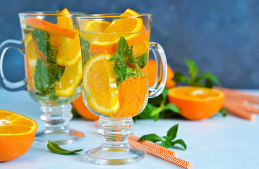 Cold summer drink. Lemonade with mint and orange on a blue background.