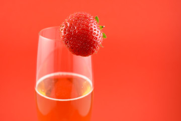 Strawberry with champagne stock images. Glass of champagne with strawberry. Champagne on a red background with copy space for text. Festive golden background. Valentines Day concept
