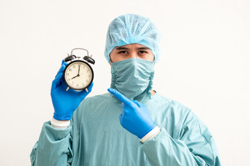 Portrait of a young surgeon with clock alarm over white background.