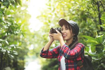 Asian girl traveler in red plaid shirt taking photo.