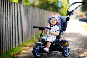 Cute adorable toddler girl sitting on pushing bicyle or tricycle. Little baby child going for a walk with parents on sunny day.