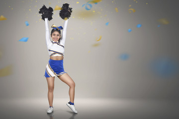 Beautiful asian cheerleader action with pom-poms