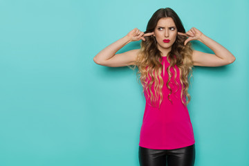 Young Woman In Pink Top Closes Her Ears With Fingers And Looking Away