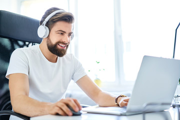 Man working on laptop with headphones from home office. Student working on laptop from dorm room