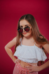 fashion concept - portrait of a beautiful little girl in big hat and sunglasses.Stylish girl in sunglasses, with long hair in shorts and a white top, on a summer vacation
