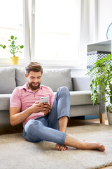 Relaxed man using phone at home sitting on the floor