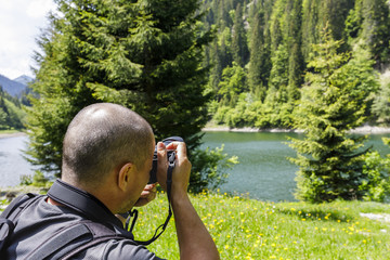Professional photographer making a picture of a mountain lake