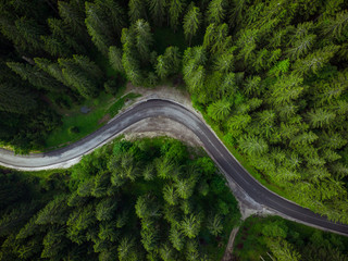 Winding road in forest, aerial drone view, road trip concept