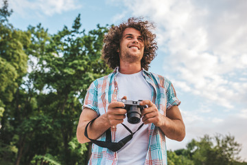 Smiling attractive young tourist man with digital camera taking photos, on a nature and sky background. Handsome man curly hair exploring nature on vacation trip. Travel, people and lifestyle concept
