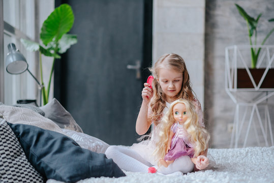 little daughter playing mother with doll