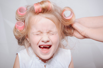 cute little girl on morning. studio shot.Happy funny child little girl with hair curlers.Portrait of preschooler girl with open mouth without milk tooth
