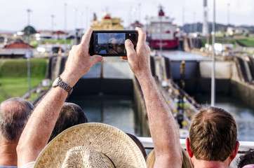 Panama - February 20, 2015: Cruise ship passengers photographing the entrance of the ships in the Panama Canal. The canal cuts across the Isthmus of Panama and is a conduit for maritime trade.