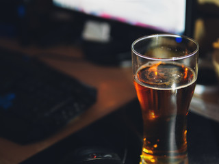 Work on the computer and drink beer. Glass of cold beer on the table