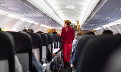 Interior of commercial airplane with passengers on seats during flight. Unrecognizable stewardess in red uniform walking the aisle. Horizontal composition.