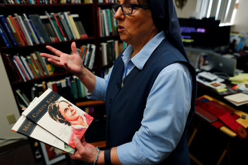 Sister Rose Pacatte, a Catholic nun who reviews movies, holds two biography's she has written while in her office in this picture taken May 24, 2018 in Culver City, California