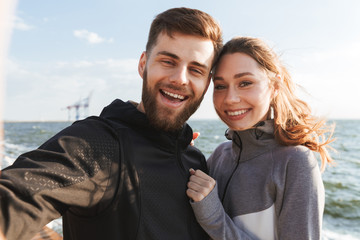 Smiling young sports couple taking a selfie