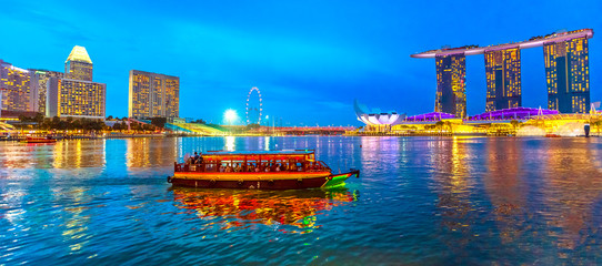Fotorolgordijn Singapore Panorama of Singapore buildings, skyscrapers and ferris wheel reflected in the sea. Tourist boat sails in the bay at evening. Singapore skyline at blue hour. Night scene waterfront marina bay.
