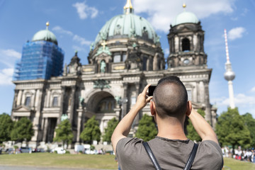 young man taking a picture of the Berlin Cathedral