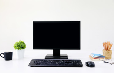 front view blank screen Computer with mouse, keyboard,pencils and tree vase in Modern office