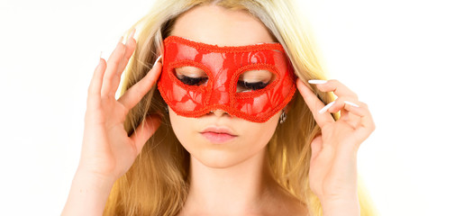 Girl with long blonde hair wears mask. Lady with long white manicure hold mask on face, white background, isolated. Mysterious woman concept. Woman on mysterious face play role game, visit masquerade.