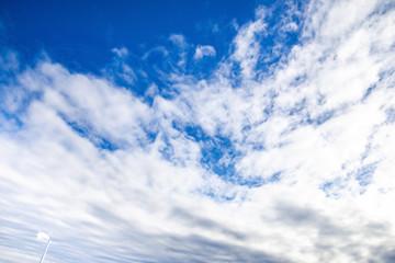青空、晴れ、雲、左下に煙突、工場