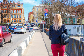 blonde woman walking through the streets of the city
