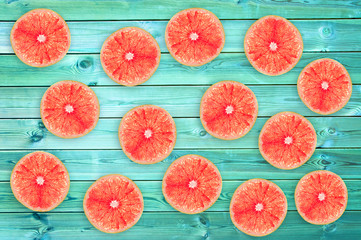 Many fresh grapefruit slices on blue wooden planks, summer background concept