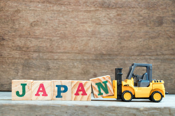 Yellow toy forklift hold letter block N to complete word Japan on wood background