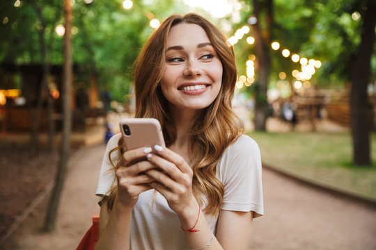 Satisfied young girl holding mobile phone while