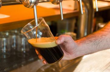 Beer being taken from the tap in brewpub, craft beer, hand of man serving beer.