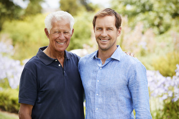 Portrait Of Senior Father With Adult Son On Walk In Park