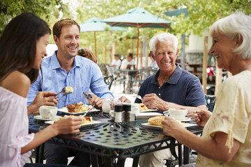 Senior Parents With Adult Children Enjoying Meal At Outdoor Cafe
