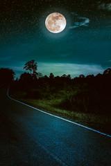Dark sky with full moon and roadway through suburban zone.