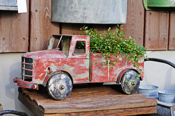 Red vintage toy truck with plant in a flower shop
