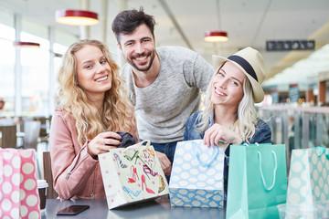 Glückliche Teenager packen Einkaufstüten aus