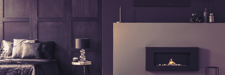Real panorama photo of a luxurious bio fireplace, silks sheets and elegant decorations in a beautiful dark purple bedroom interior