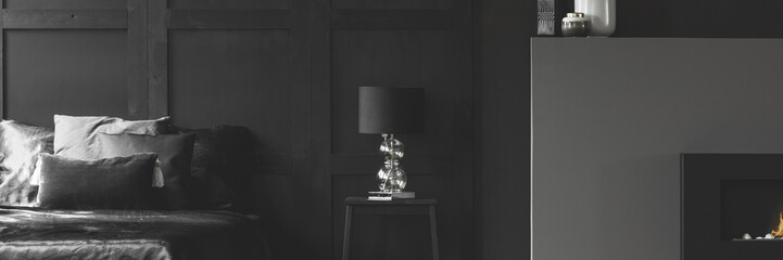Real header photo of an elegant lamp with a glass base on a simple night stand between a cozy bed and fireplace in black apartment room interior