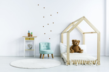 Teddy bear on wooden bed next to blue chair in white kid's bedroom interior. Real photo