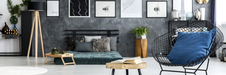 Black diamond chair with blue pillow and open book on end table standing in dark room interior photo with blurred background