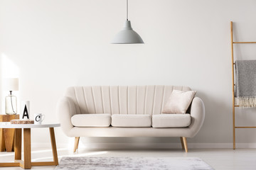 Real photo of a beige sofa standing in a simple living room interior under a lamp and next to a table and ladder