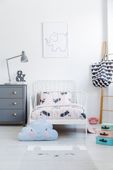 Blue cloud pillow in front of white bed next to grey cabinet in kid's bedroom interior. Real photo
