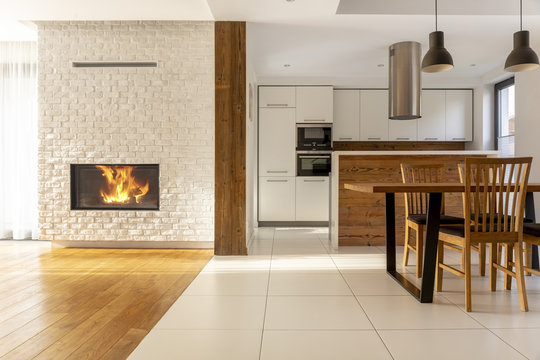 Fireplace in spacious white house interior with wooden chairs at table near kitchen. Real photo