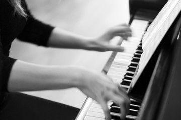 Close-up of a music performer's hand playing the piano. Blurred, black and white, out of focus