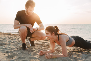 Happy young sport couple doing plank exercise