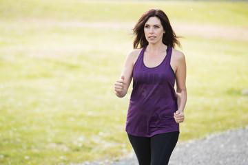 Pretty mature woman running outside
