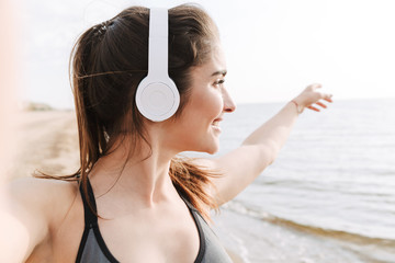 Smiling young sportswoman with headphones