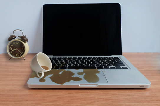 Coffee Cup spill out on Laptop Keyboard on wooden floor, Accident computer repair concept.