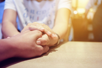 Woman and man holding hands together with love on wooden table in restaurant