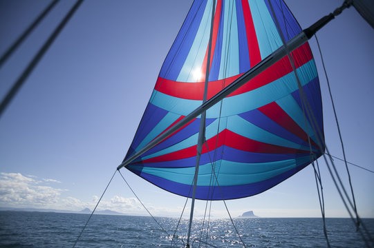 Flying a colorful spinnaker on a seaworthy sailing yacht